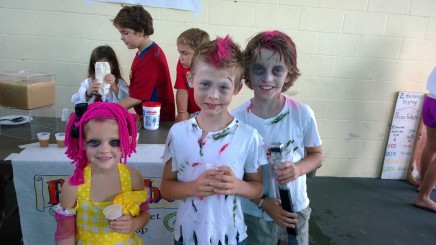Ava Harlan, Payton Harlan and Jeremiah Harlan sip Butter-Beer at the Fall Festival Oct. 26. The siblings came to the party as pink-haired un-dead zombies.