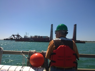 Bradenton Beach Commissioner Jack Clarke stands on the deck of the dredge barge California.