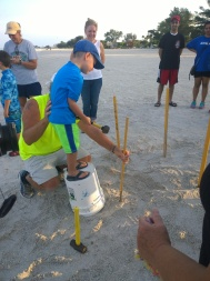 Ryan Weatherwax, 5, visiting from Saudi Arabia, stands on a bucket and hammers a stake marking a sea turtle nest. AMITW volunteer Glenn Wiseman assists.