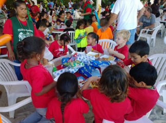 Children invited to the Christmas party are served lunch by Sandbar Restaurant staff and volunteers before Santa arrived to hand out presents. The lunch included juice, chicken fingers and french fries.