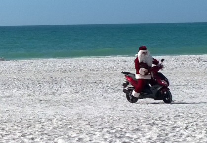 After leaving the parking lot, Santa made a second surprise entrance to the party on a scooter. He zipped across the beach on a scooter, greeting children before taking his seat for gift-giving.