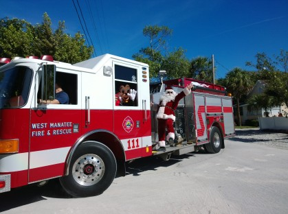 Santa arrives at noon on a fire truck.