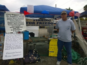 Mark Coarsey, president of the Fishing for Freedom Manatee chapter, stands in front of a fishing net exhibition Nov. 9 at the Stone Crab Festival in Cortez.