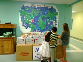 Anna Maria Elementary School students look at a map above donations bound for the Philippines.